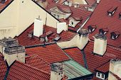 Terracotta tiled roofs with chimneys and dormer windows of city or town houses buildings on roofscape background poster