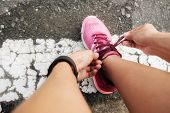 Running shoes. Barefoot running shoes closeup. Female athlete tying laces for jogging on road in minimalistic barefoot running shoes. Runner getting ready for training. Sport lifestyle. poster