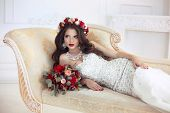 Beautiful brunette Bride wedding Portrait. Red lips makeup. Long wavy hair style. Expensive diamond jewelry. Bridal bouquet of flowers. Elegant lady lying on modern sofa in white interior. poster