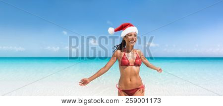 Christmas bikini woman happy on tropical beach in Santa hat. Summer vacation banner with copy space. Asian girl with sexy body on blue sky and ocean water. Travel vacation holidays under the sun.