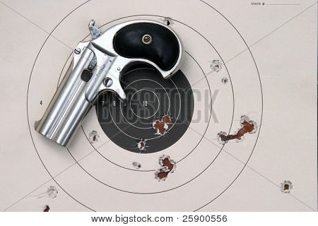 Circa 1889, Model 95, Type II Model 3 Double Derringer, a paper target with bullet holes in it