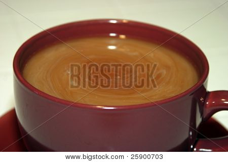 Large Cup and Saucer of fresh brewed coffee with a vortex of cream swirling around