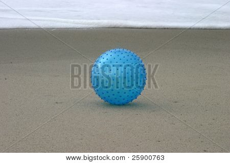 spikey blue beach ball on the beach