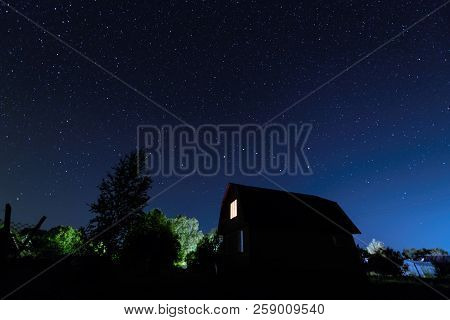 Blue Dark Night Sky With Many Stars Above Wooden House At Summer Night.