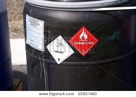 black plastic drum with hazardous waste poster