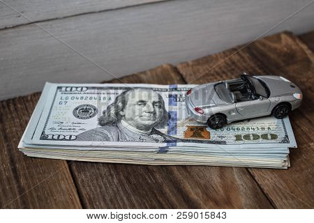 A Stack Of One Hundred Dollar Bills On Wooden Background