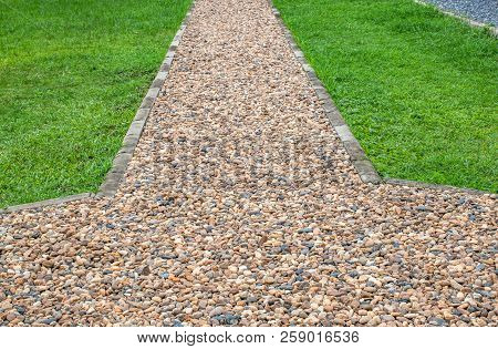 Walkway Paved With Gravel Beside A Green Lawn.