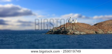 Lighthouse and agios Nikolaos church on rocky land. Kea,Tzia the sunny island, Greece. Blur cloudy sky background, banner.