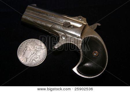 1889 darringer pistol with an 1887 Morgan silver dollar on blue velvet