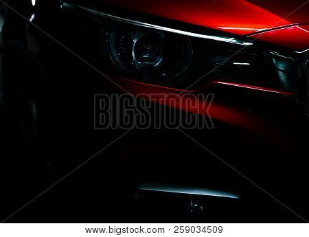 Closeup Headlight Of Shiny Red Luxury Suv Compact Car. Elegant Electric Car Technology And Business