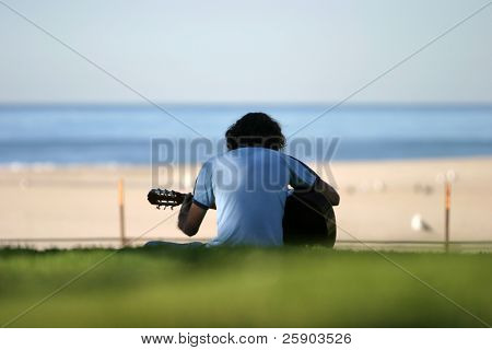 an unidentifiable person plays guitar on a grassy knoll by the beach