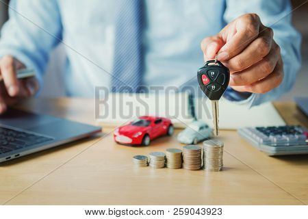 Car Dealer Hand Holding Key. Concept Car Insurance And Financing