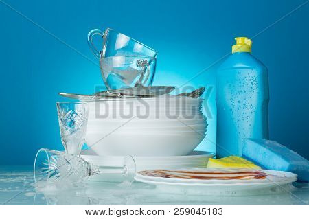 The Process Of Washing Dishes On Blue Background, Plates, Washcloths