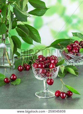 Fresh Ripe Sweet Cherry In Crystal Bowl Against The Background Of Leaves