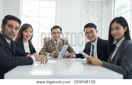 A Confident Business Team Of Mixed Ages And Ethnicity Are Holding A Meeting In A Modern Office. They