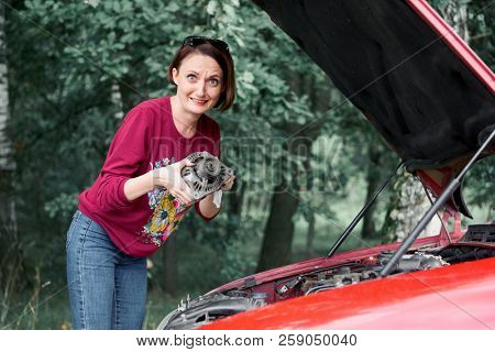 a young girl stands at a broken car and holds a bad spare part, an electric generator, does not understand how to repair