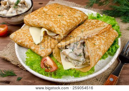 Pancakes Stuffed With Mushrooms And Cheese With Cream Sauce. Traditional Russian Food
