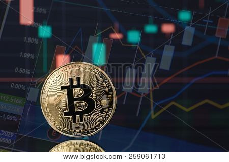 Bitcoin Cryptocurrency Coin Token In Gold With Financial Stock Market Charts In The Background. Conc