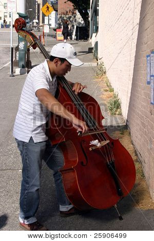 "a person plays a cello for ""spare change"" in seattles historic ""Pike place market"" aka ""farmers market"""