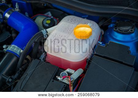 Plastic Cooling Liquid Tank In Car Engine. Antifreeze Radiator Liquid