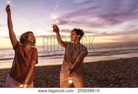 Laughing Friends Playing With Sparklers At The Beach During Sunset