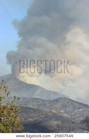 Thick Noxious Curling Black and Brown smoke and flames rise as fire destroys and devistates home and land in the Santiago Canyon California wild fires