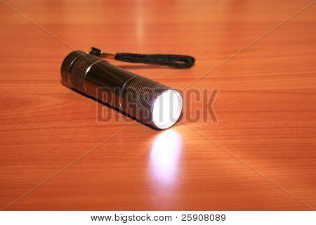 a Mulit Bulb LED flashlight lays on a table emitting bright light while turned on