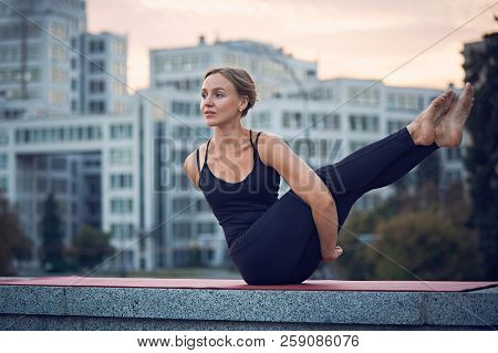 Beautiful Young Woman Practices Yoga. Variation Of Navasana With Twist - Boat Pose Outdoors Against