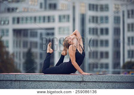 Beautiful Woman Practices Yoga Asana Eka Pada Padangustha Dhanurasana Pose Outdoors Against The Back
