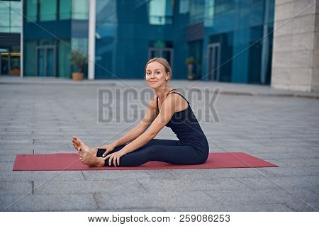 Beautiful Young Woman Prepares To Practice Yoga Outdoors Against The Background Of A Modern City