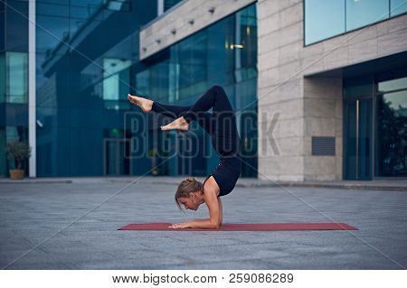 Young Woman Practicing Yoga, Standing In Vrischikasana Scorpion Pose Outdoors Against The Background
