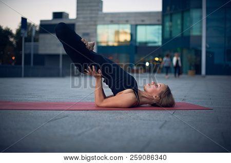 Beautiful Young Woman Practices Yoga Asana Padma Sarvangasana - Shoulderstand Lotus Pose Outdoors Ag