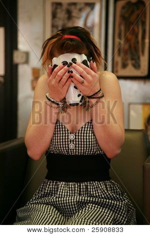 "a beautiful young woman wears a plastic ""dog mask"" while in a ""tattoo parlor"" because it makes a cool portrait"