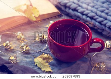 Red cup of tea, garland and wool blanket