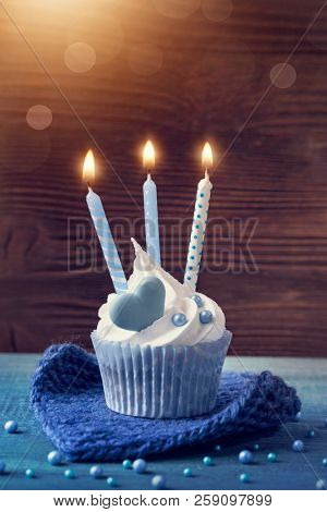 Cupcake with a blue candles for birthday
