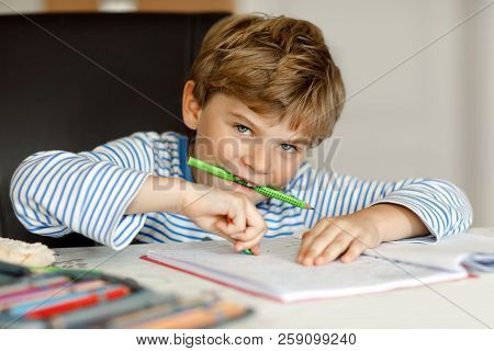 Portrait Of Cute Healthy Happy School Kid Boy At Home Making Homework. Little Child Writing With Col
