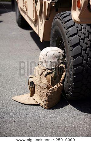 us military flack jacket and helmet lay against a h1 humvee