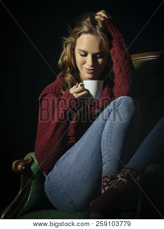 Photo Of A Beautiful Young Woman Drinking Coffee Sitting On An Old Leather Chair.