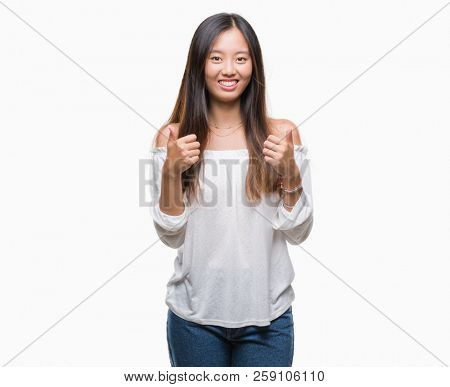 Young asian woman over isolated background success sign doing positive gesture with hand, thumbs up smiling and happy. Looking at the camera with cheerful expression, winner gesture.