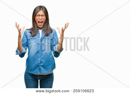 Young asian woman wearing glasses over isolated background crazy and mad shouting and yelling with aggressive expression and arms raised. Frustration concept.