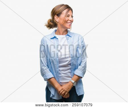 Middle age senior hispanic woman over isolated background looking away to side with smile on face, natural expression. Laughing confident.