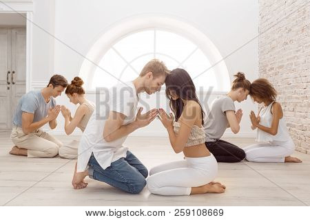Fitness, Yoga And Healthy Lifestyle Concept - Group Of People Doing Lotus Seal Gesture And Meditatin