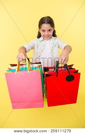 Check Out Her Shopping Packages. Girl Carries Shopping Bags Yellow Background. Child Cute Shopaholic