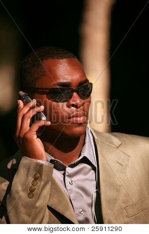 a well dressed african american man recieves messages on his cell phone outside while listening on his personal digital music player