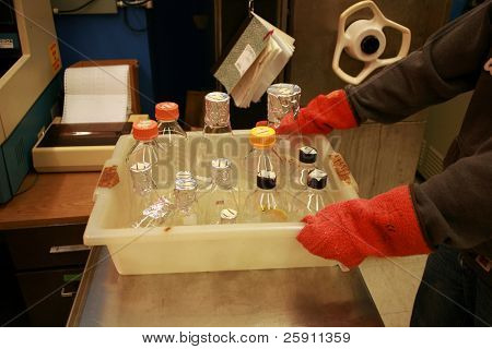 a person takes glass wear out of an autoclave in a science lab