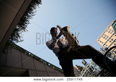 a musician plays his saxaphone for all to hear and enjoy
