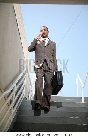 a business man talks on his cell phone as he walks down stairs