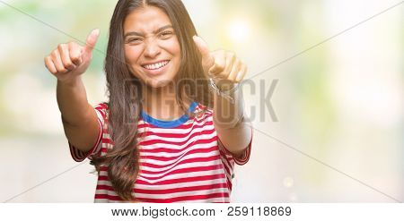 Young beautiful arab woman over isolated background approving doing positive gesture with hand, thumbs up smiling and happy for success. Looking at the camera, winner gesture.