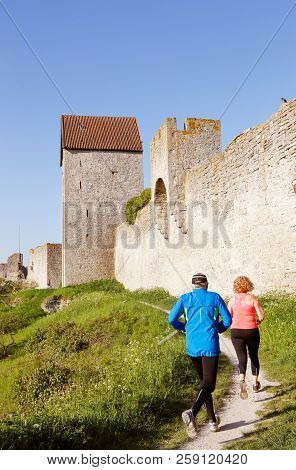 Visby, Sweden - May 13, 2016: A Man And A Woman Jog In The Morning Sun Next To The Visby City Wall I
