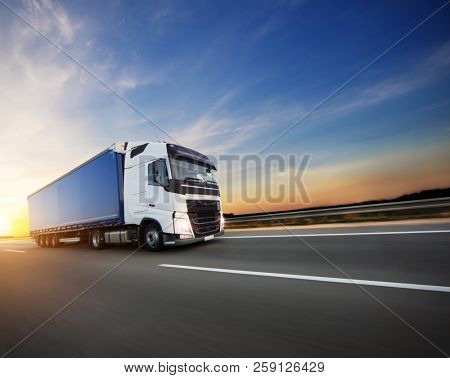 Loaded European truck on motorway in beautiful sunset light. On the road transportation and cargo.